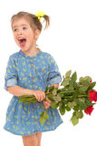 Charming little girl holding a bouquet of red roses. Royalty Free Stock Image