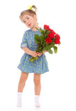 Charming little girl holding a bouquet of red roses. Stock Images