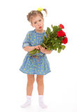 Charming little girl holding a bouquet of red roses. Royalty Free Stock Photo