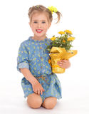 Charming little girl holding a flower bouquet. Stock Photo