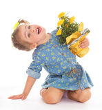 Charming little girl holding a flower bouquet. Stock Photos