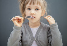 Charming little girl holding a fork Stock Images