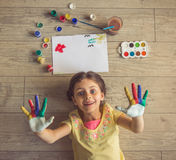 Charming little girl at home. Top view of charming little girl showing her painted palms, looking at camera and smiling while lying on the floor near the royalty free stock images