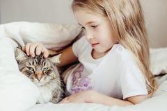 Charming little girl hugging her cat lying Stock Photography