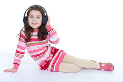 Charming  little girl is listening to music. Stock Photos