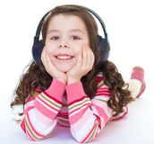 Charming  little girl is listening to music. Royalty Free Stock Images