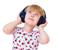 Charming little girl loves to listen to music Stock Photography
