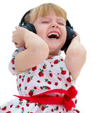 Charming little girl loves to listen to music Stock Image
