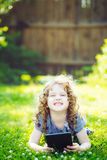 Charming little girl lying on the grass and holds in hands tablet Royalty Free Stock Images