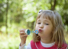Charming little girl making soap bubbles Stock Photo