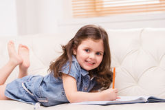 Charming little girl opened notebook. Stock Photos