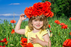 Charming little girl in a poppy field with a bouquet of poppies on her head Royalty Free Stock Photos