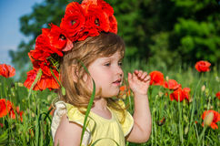 Charming little girl in a poppy field with a bouquet of poppies on her head Stock Photo