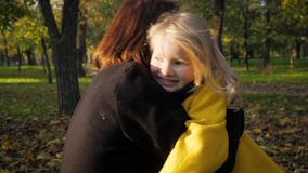Charming little girl rarely runs into arms of her beloved mother while relaxing in fresh air in an autumn park amid