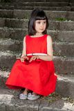 Charming little girl in a red dress Stock Images