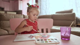 A charming little girl in a red dress paints with watercolor at the table. stock footage