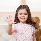 Charming little girl showing five. Royalty Free Stock Images