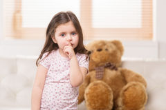 Charming little girl showing silence sign. Stock Photo