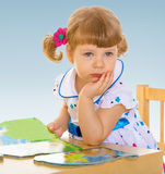 Charming little girl. Sitting at a desk and reading books royalty free stock image