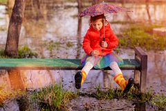 Little girl with umbrella on bench in puddle Stock Photos