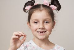 Little girl and a milk tooth royalty free stock photos