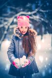 Charming little girl with a snow balls.  Stock Photos