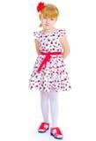 Charming little girl standing leg thrust forward Stock Images