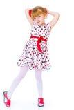 Charming little girl standing leg thrust forward Stock Photography