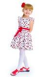 Charming little girl standing leg thrust forward Royalty Free Stock Photo