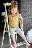 Charming little girl is standing on a white ladder. She is smiling royalty free stock photos