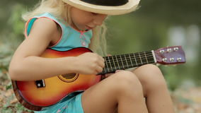 Charming little girl in straw hat playing on toy stock video