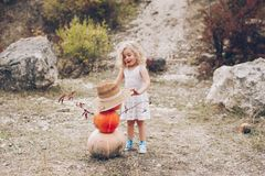 Charming little girl in a straw hat, wicker chair, pumpkins Stock Photography