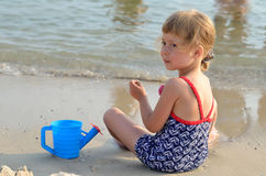 Charming little girl in a swimsuit playing on the sandy beach. Stock Images