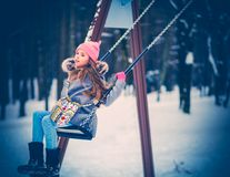 Charming little girl on swing in snowy winter.  stock images