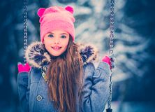 Charming little girl on swing in snowy winter.  royalty free stock image