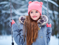 Charming little girl on swing in snowy winter.  Stock Photography