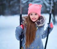 Charming little girl on swing in snowy winter.  Stock Image
