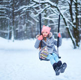 Charming little girl on swing in snowy winter.  stock photo