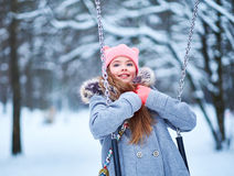 Charming little girl on swing in snowy winter.  royalty free stock photos