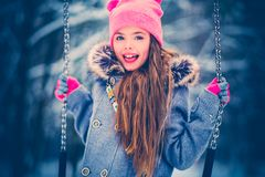 Charming little girl on swing in snowy winter.  royalty free stock photo