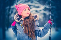 Charming little girl on swing in snowy winter.  royalty free stock images