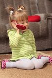 Charming little girl talking on the phone Stock Photos