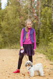 Charming little girl walking with puppy in park Stock Photography