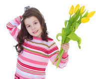 Charming little girl with yellow tulips. Stock Photo