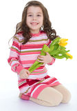 Charming little girl with yellow tulips. Royalty Free Stock Photos