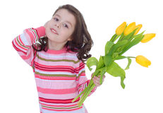 Charming little girl with yellow tulips. Royalty Free Stock Image