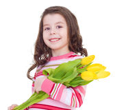 Charming little girl with yellow tulips. Stock Images