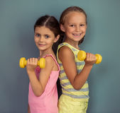 Charming little girls. Two cute little girls are holding dumbbells, looking at camera and smiling, standing on gray background Stock Image