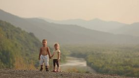 Charming little kids at the age of 3-5 are holding hands while standing at the edge of the mountains during the sunset.