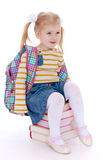 Charming little schoolgirl with satchel behind him Stock Images
